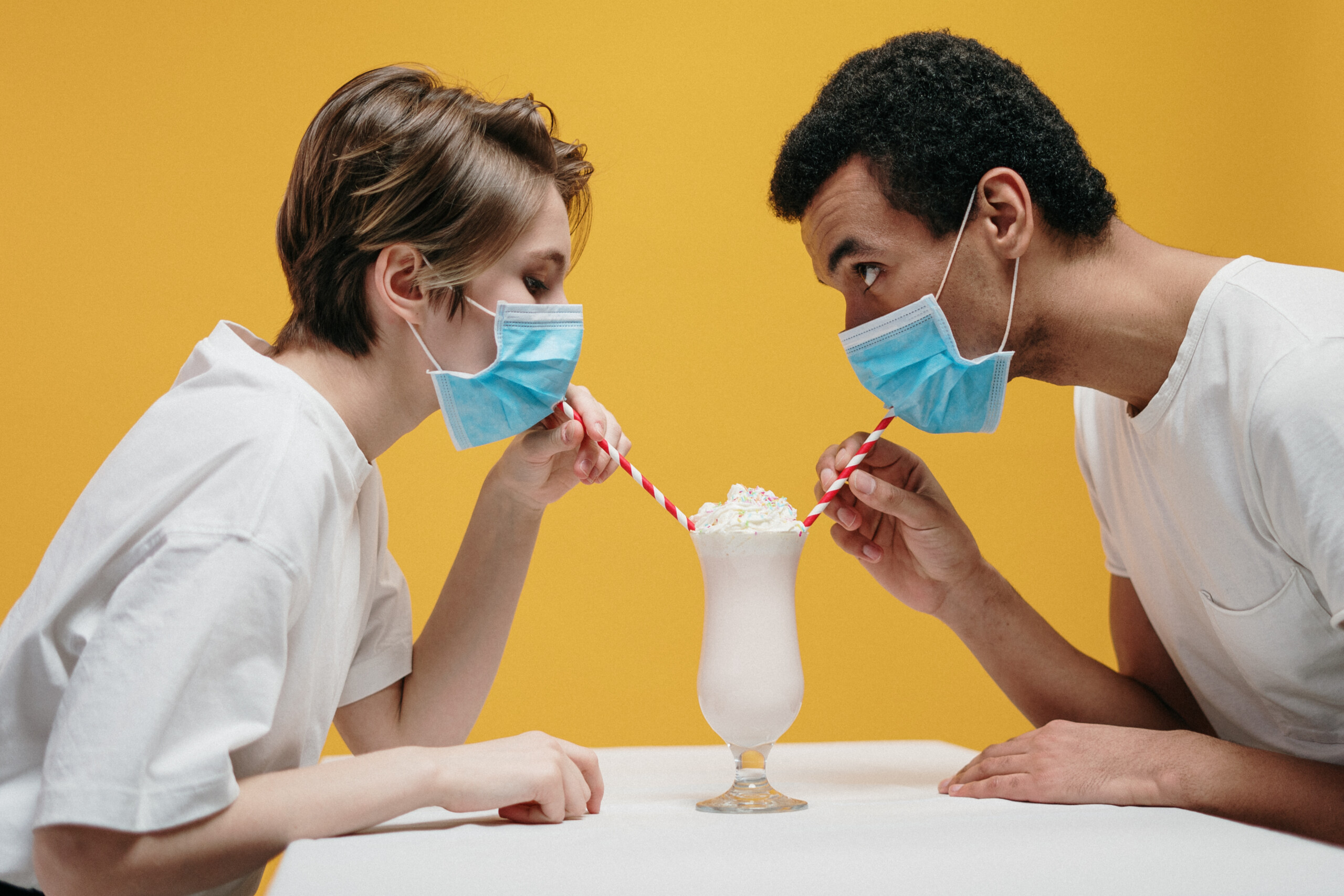couple wearing face masks drinking a milkshake with a straw.